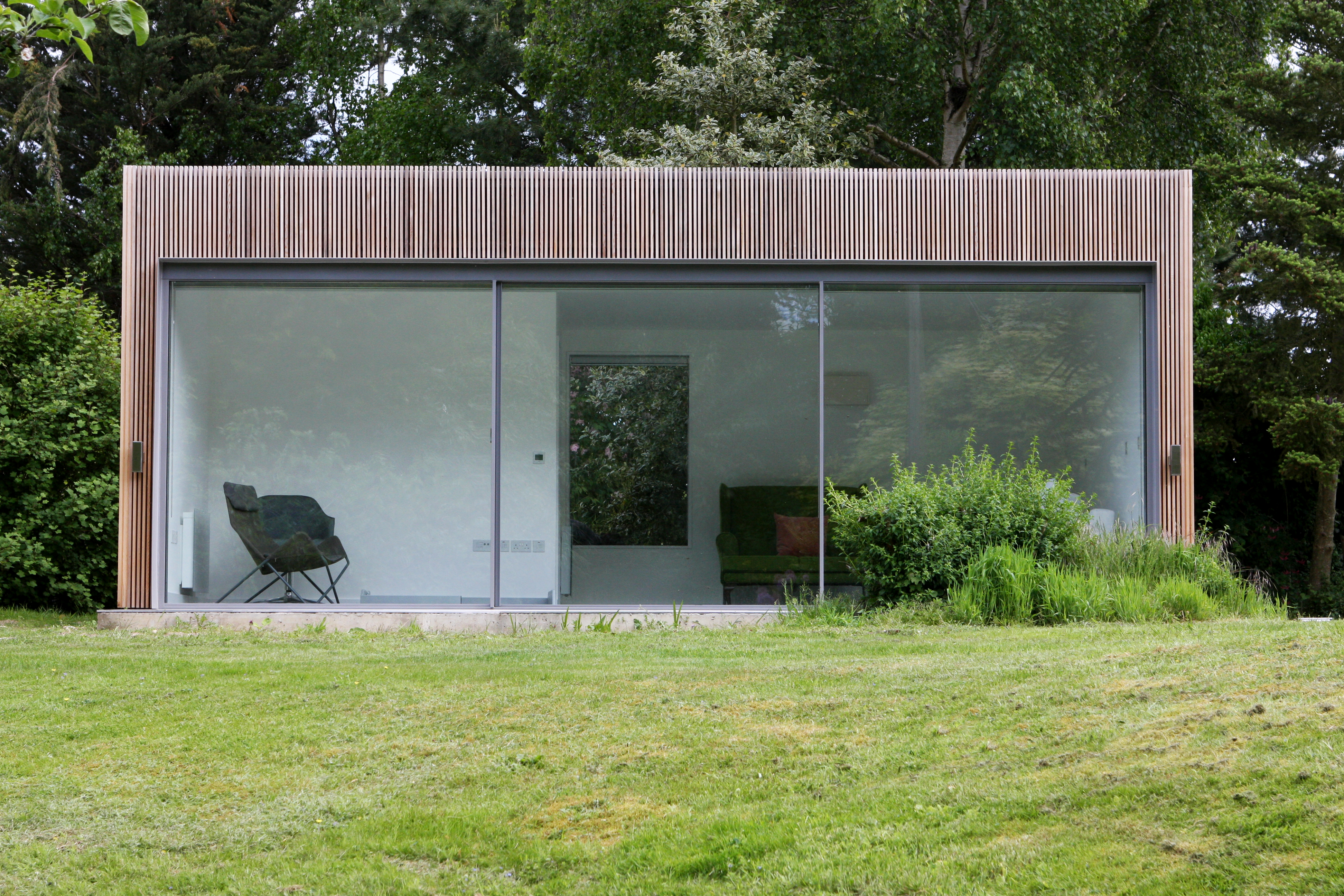 minimal windows to a garden with the two outer windows fixed, middle pane sliding