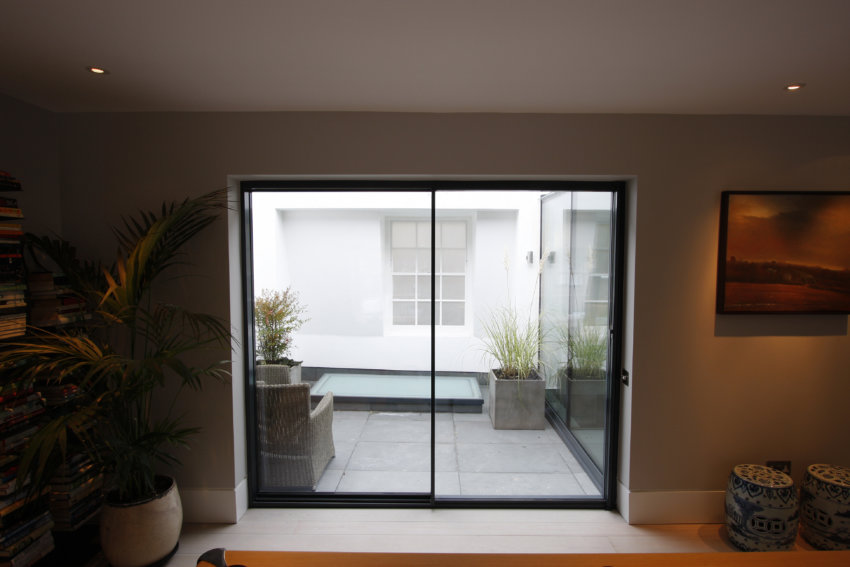 Slim frame sliding glass doors used on a new roof extension to maximise natural light