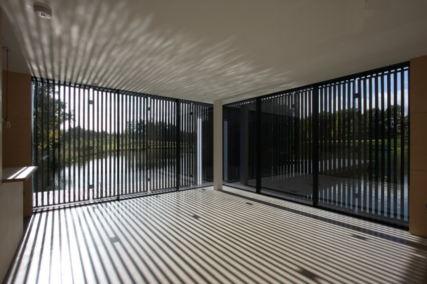 Timber shutters over the glazing still allow natural light through without shutting away the views.