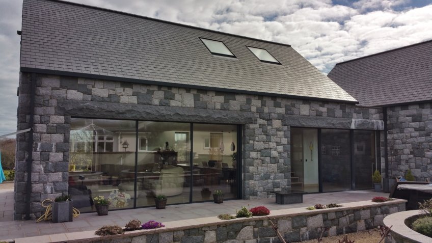 Slim frame sliding glass doors to a traditional stone house in Guernsey