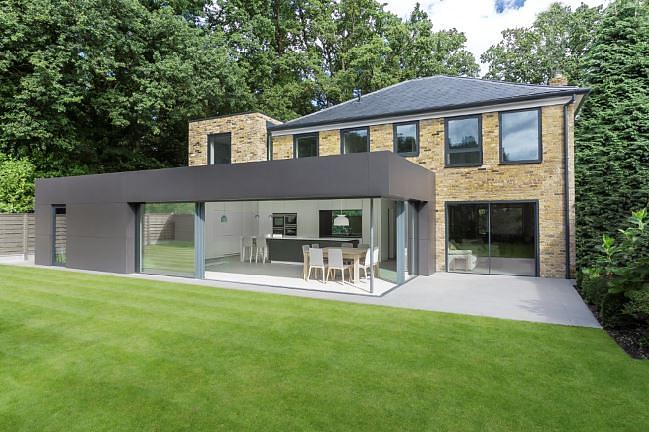 Contemporary extension to a traditional home using minimally framed sliding glass doors