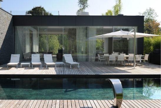 Oversized aluminium sliding glass doors designed as floor to ceiling to create entire sliding glass walls