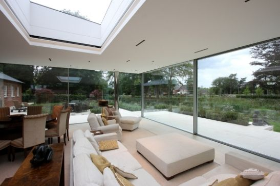 internal view of luxury glass extension with floor to ceiling sliding glass doors and a large fixed rooflight