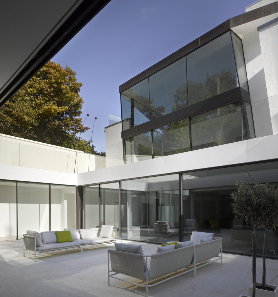 Two storey glass box with minimal windows sliding glass doors