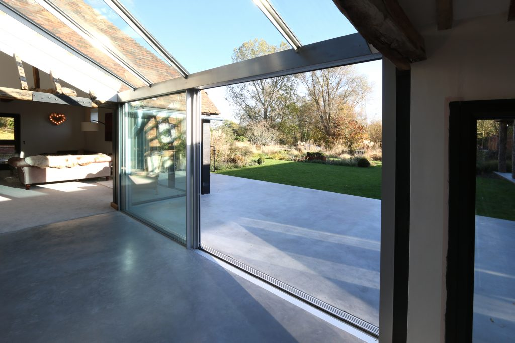 Modern barn conversion with structural glass roof and sliding glass doors