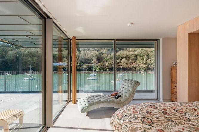 bedroom with corner opening slim sliding door onto a balcony
