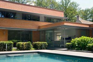 header image of a red brick house with minimal windows corner opening slim sliding doors