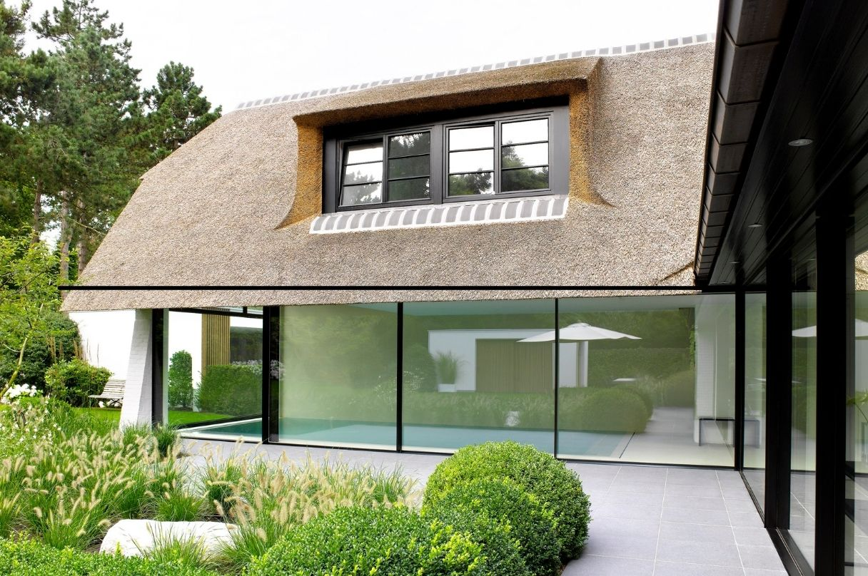 minimal windows sliding door system on thatched roof pool house