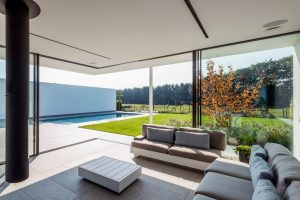 corner opening sliding glass doors with a flush threshold leading to a garden with a pool