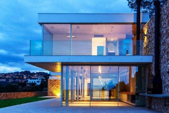 floor to ceiling glass sliding doors and an upper floor balcony with frameless glass balustrades