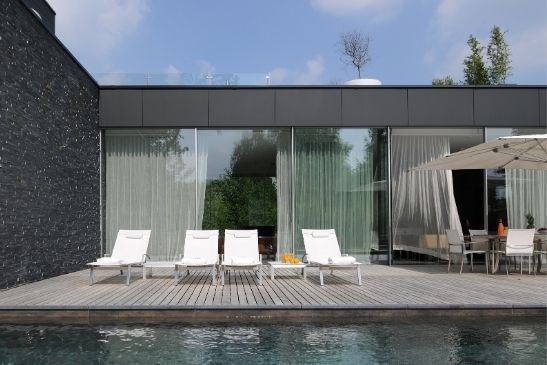 large slim sliding glass doors next to a pool decking