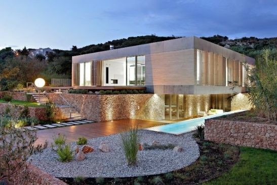 luxury residential home with pool made form natural materials to blend into the landscape featuring floor to ceiling glazing