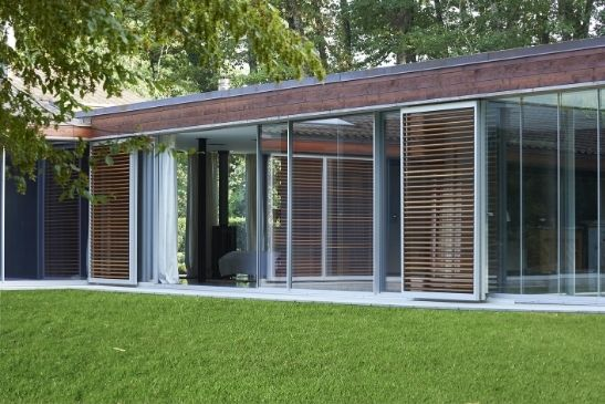 luxury woodland retreat with floor to ceiling sliding glass doors with flush thresholds and wooden external shutters