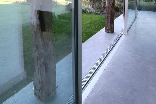 minimal windows integrated drainage system with silver slot drain by sliding glass doors