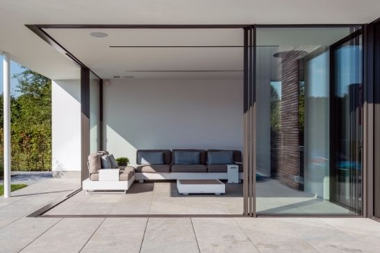 minimal windows slim sliders with brown aluminium framing around the sliding glass doors