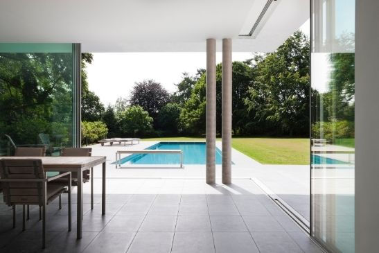 minimal windows slim sliding glass doors ina corner configurations connecting the dining area and outdoors