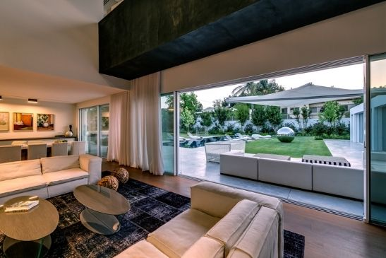 monochrome living room with large slim sliding glass doors leading out to a luxury garden with a pool