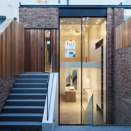 contemporary home extension on a terraced property in a conservation area in London featuring minimal windows 4+ double height sliding glass doors