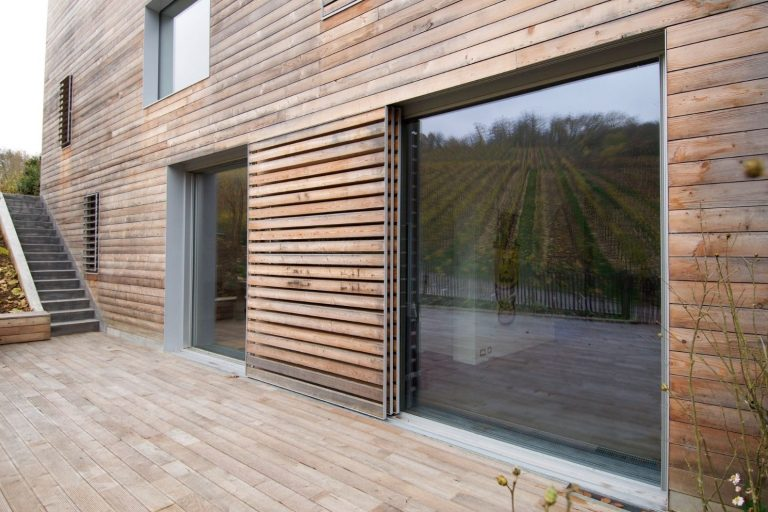 timber view with minimal windows sliding glass doors in a pocket configuration and external timber solar shading solutions