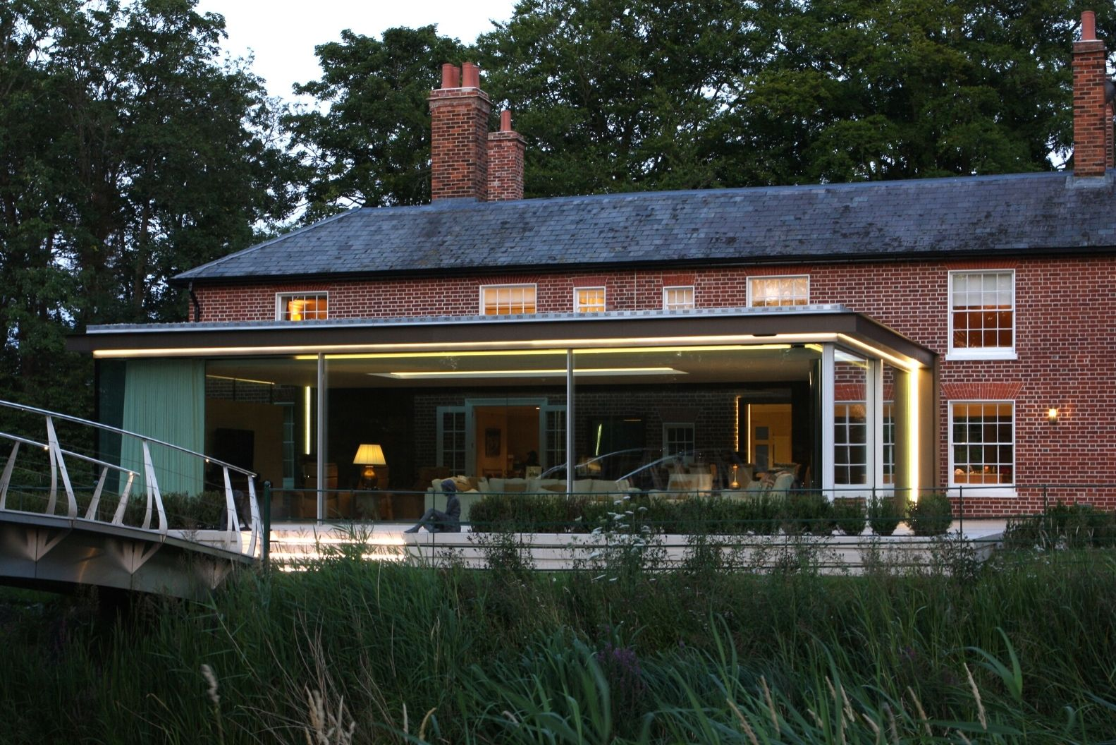 banner image of a contemporary glass extension with minimal windows sliding glass doors on a traditional home located in a conservation areas