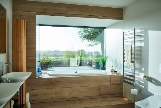 bathroom with natural wood building materials and a large window displaying elements of biophilic design using an aluminium fixed window