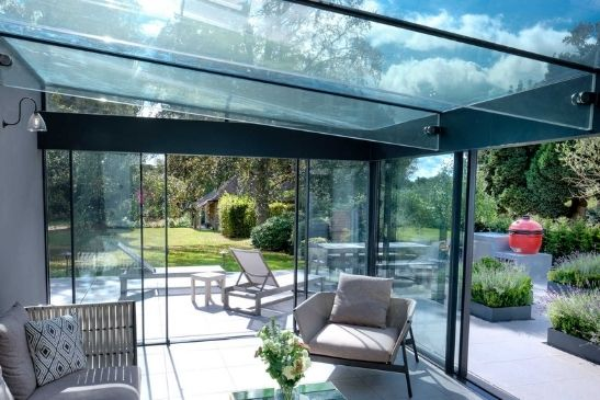 contemporary extension with sliding glass doors from minimal windows and a structural glass roof