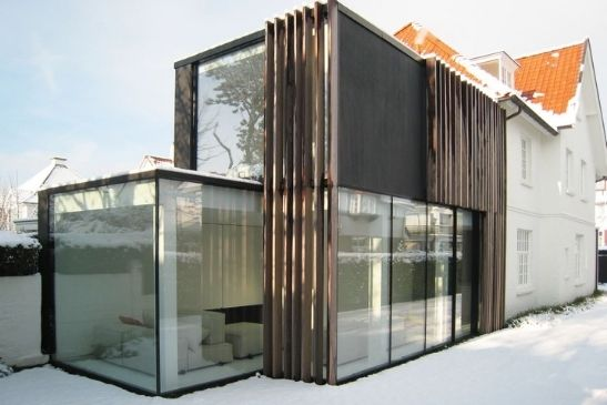 contemporary home extension with heated sliding glass doors being used as a heat source and to prevent show and ice build up