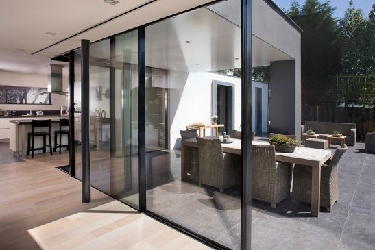 contemporary new build home with tall sliding glass patio doors from minimal windows