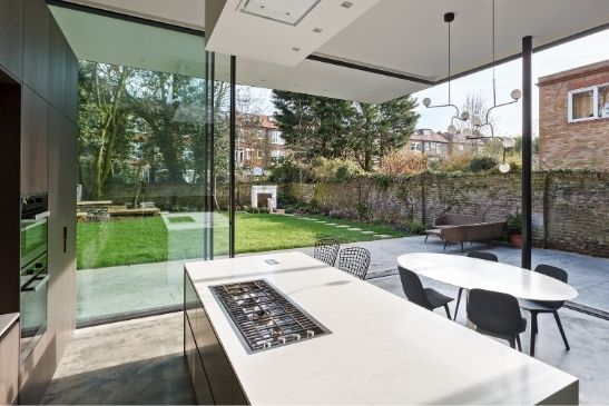 floor to ceiling minimal windows sliding glass doors on a contemporary glass extension on a London home
