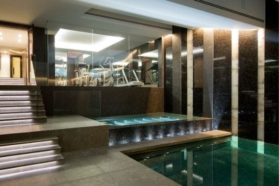 heated glass used as a divider between and indoor pool and indoor gym area