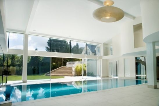 heated sliding glass doors used in a glass extension indoor pool area