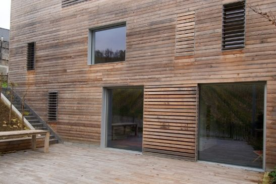 minimal windows pocket sliding glass doors and building with external timber cladding and timber solar shading solutions