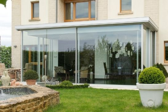 north facing glass box extension with heated sliding glass doors used as a heat source to keep the internal space warm