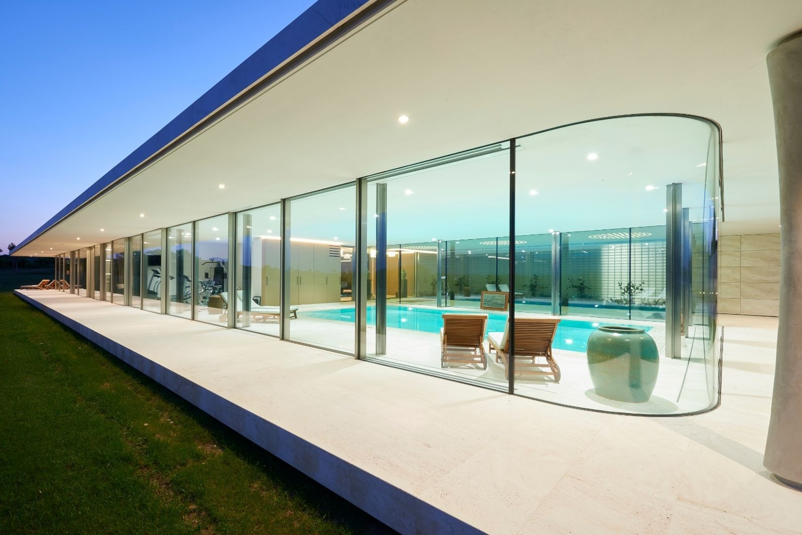 sliding glass doors by an indoor pool area in a luxury new build home with curved glass corners