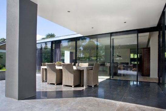 slim sliding glass doors leading out to a contemporary patio space perfect for entertaining guests