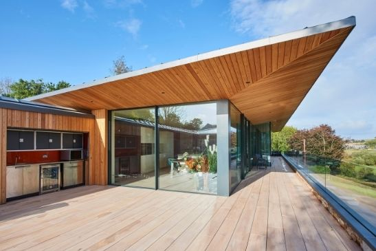 wooden eaves solar shading solution over an external balcony and terrace area with frameless glass balustrades and large aluminium sliding glass doors