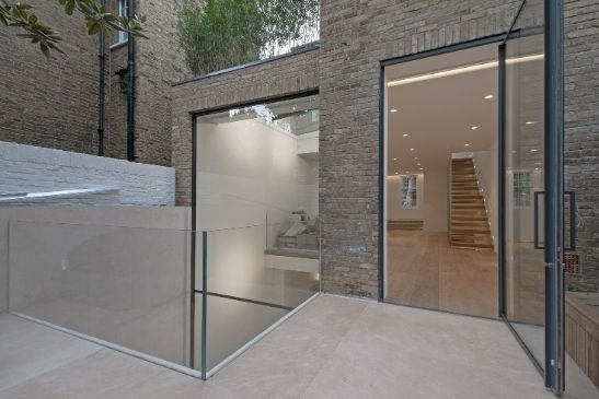 minimal windows pivot door, frameless glass balustrade and double height glazing next to a void which lets light into the basement