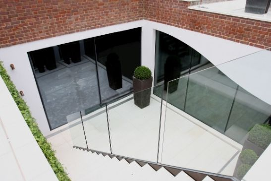 luxury basement renovation with minimal windows slim sliding doors leading to stairs up to the garden