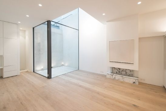 modern and minimal basement renovation with an internal courtyard surrounded by glass to let in natural light