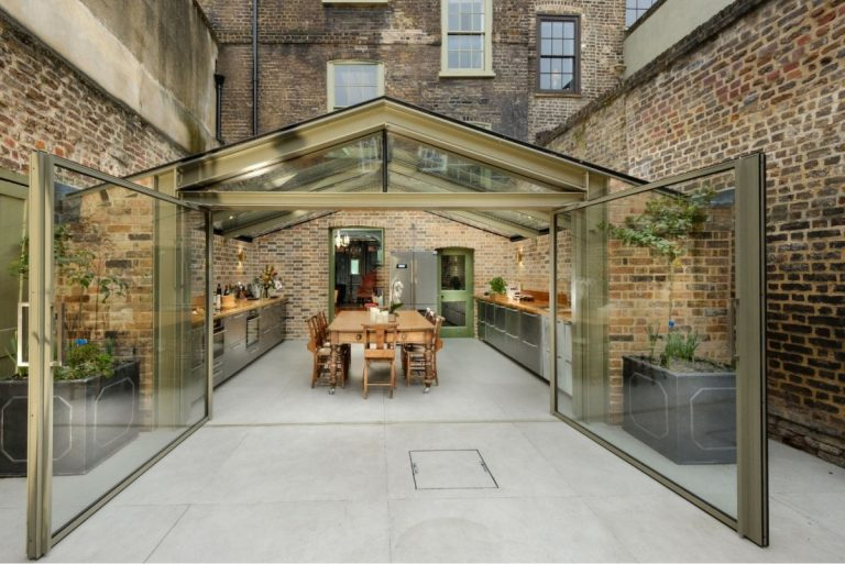 banner image of minimal windows pivot doors in a rustic glass extension
