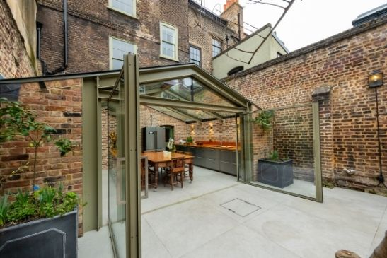 contemporary rustic extension with exposed prick walls, a glass roof and aluminium pivot doors from minimal windows