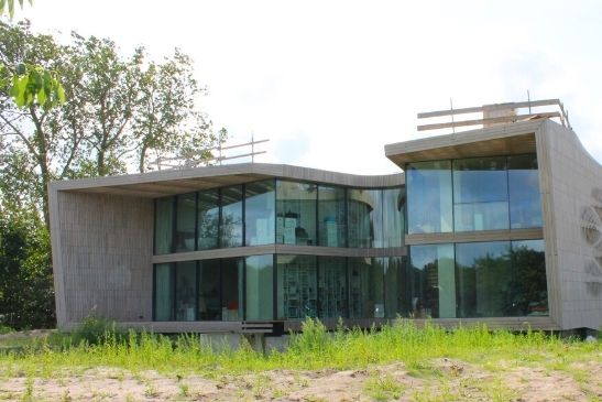 impressive glass facade at the rear of this luxury home with curved glass and minimal windows slim sliding glass doors