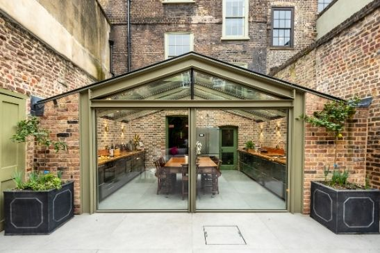 large glass pivot doors from minimal windows in a glass extension with exposed brick walls