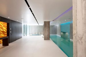 luxury basement window with an indoor pool and minimal windows sliding doors in the far corner for natural light