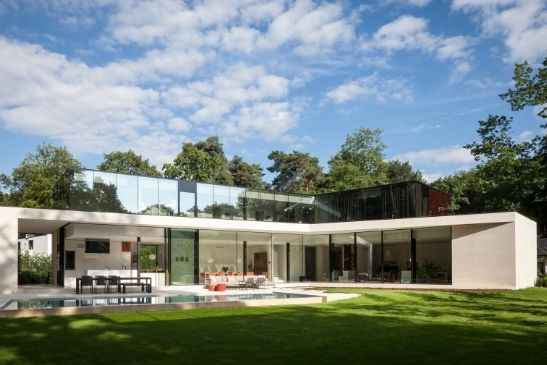 luxury home with an outdoor swimming pool and glass walls that include multiple minimal windows aluminium sliding glass doors