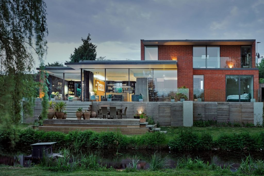 luxury new build home in a conservation area and a flood zone with minimal windows aluminium sliding glass doors used to create glass walls