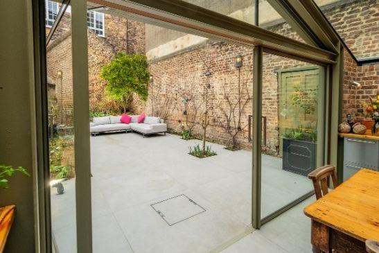 minimal windows pivot doors with a flush threshold and olive grey aluminium frames