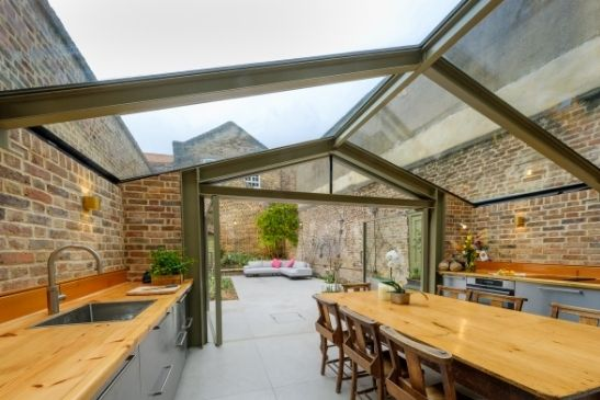 olive grey framed pivot doors from minimal windows in a modern glass home extension