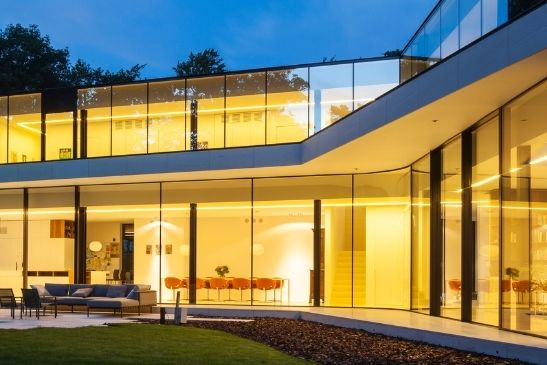 structural glazing including a curved glass pane and minimal windows slim sliders create glass walls with moving elements
