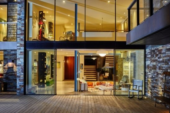 sliding biparting glass doors as part of a double height glass facade in a luxury new build home y the coast